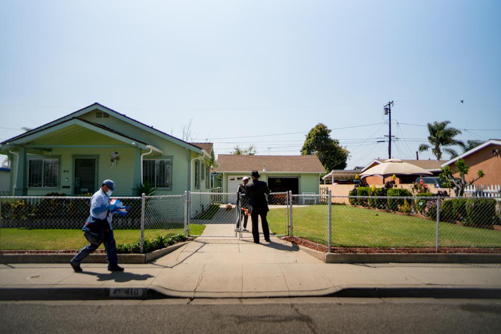 Robert Lee Johnson speaks with a resident in his childhood neighborhood. He says Compton felt like a