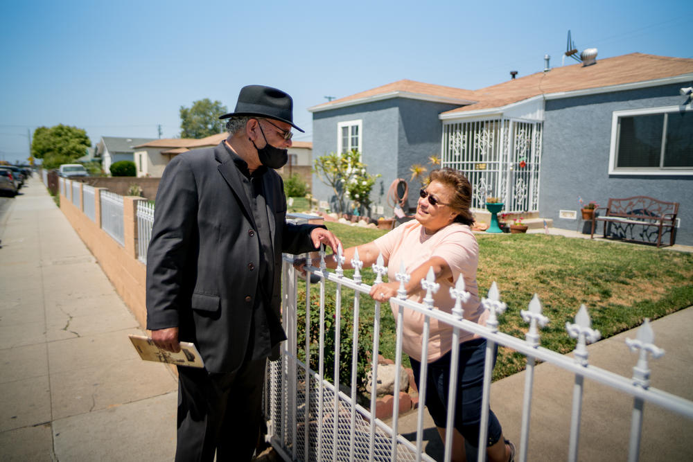 Robert Lee Johnson greets his childhood friend and neighbor, Yolanda Segura. The two met in 1961 when Robert first moved to the neighborhood at age 5.