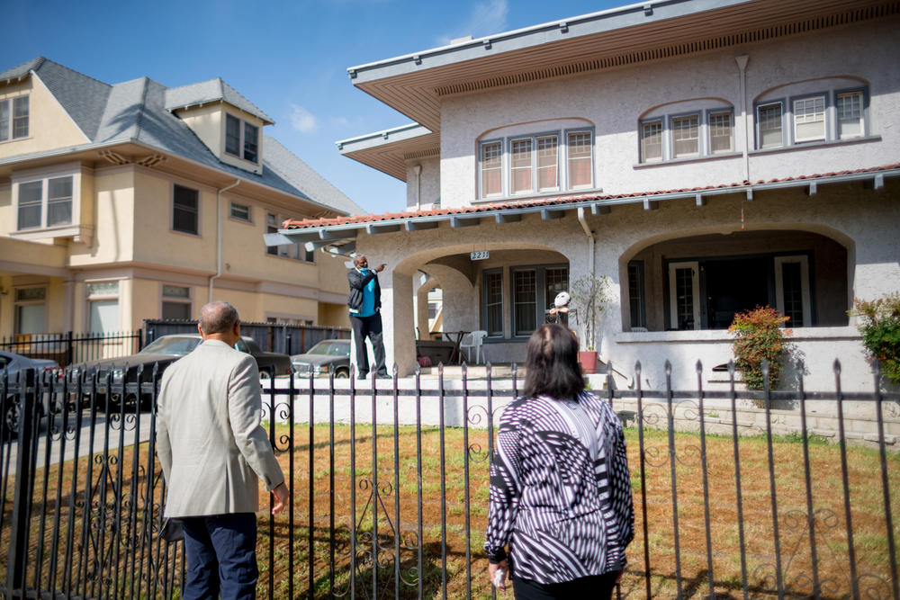 Outside the former home of their grandfather, Norman Houston, Ivan Houston and Kathi Houston-Berryman speak with a current resident who points next door to where <em>Gone with the Wind </em>actress Hattie McDaniel once lived.