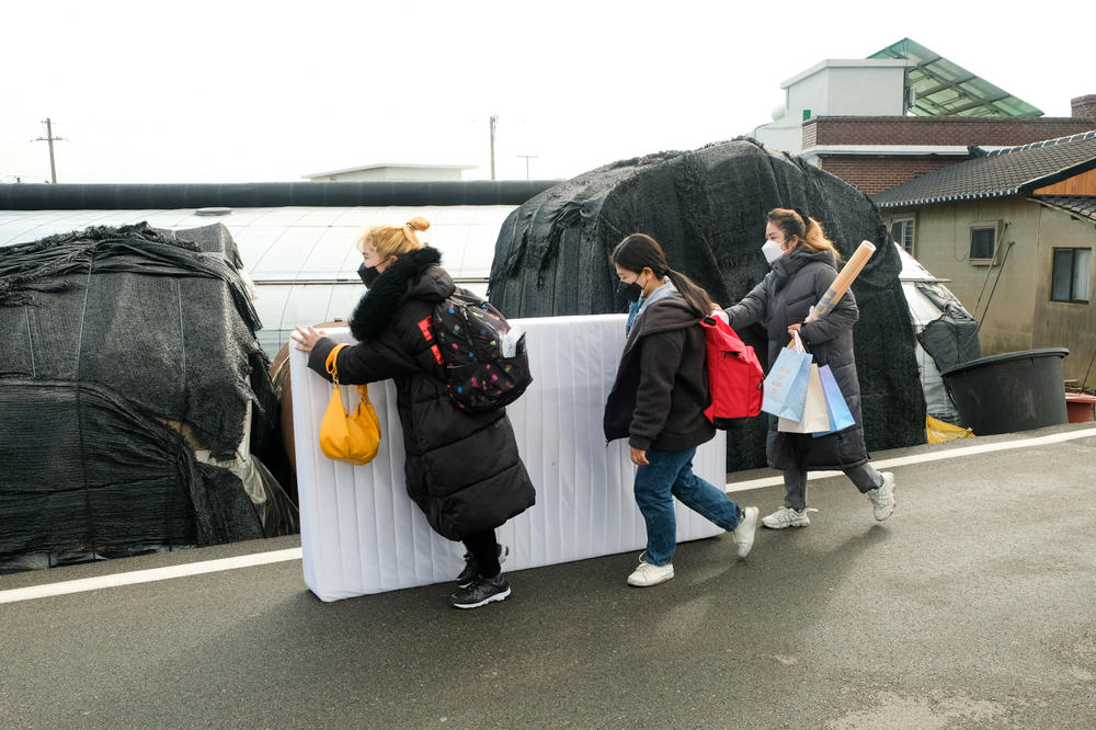 Labor rights activists help a Cambodian migrant farm worker move her belongings out of her dwelling in Miryang, South Korea. The activists help the migrants, who complain of poor treatment, find new jobs.