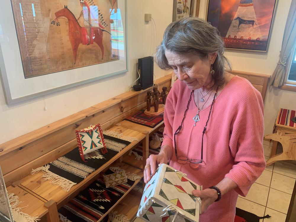 Angelika Harden-Norman holds a parfleche box made by her late husband, Darrell Norman. Harden-Norman made both traditional and modern Blackfeet artwork. Parfleche boxes are painted containers made from animal hide. They were used by Native Americans to carry items as they traveled.