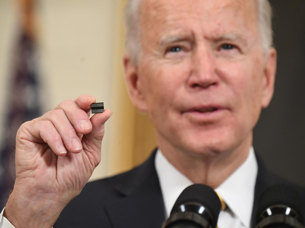 President Biden holds a microchip before signing an executive order on securing critical supply chains in February. A shortage of chips after a surge in demand hampered key sectors such as carmakers.