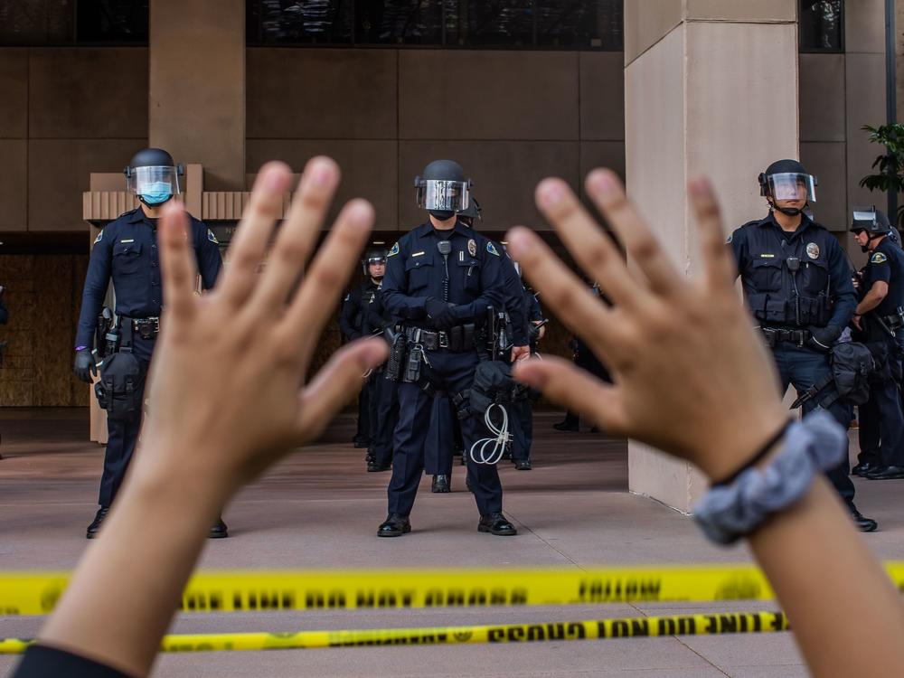 A demonstrator holds her hands up while she kneels in front of the Police at the Anaheim City Hall on June 1, 2020 in Anaheim, California. Reform pressures have many cops leaving the job.