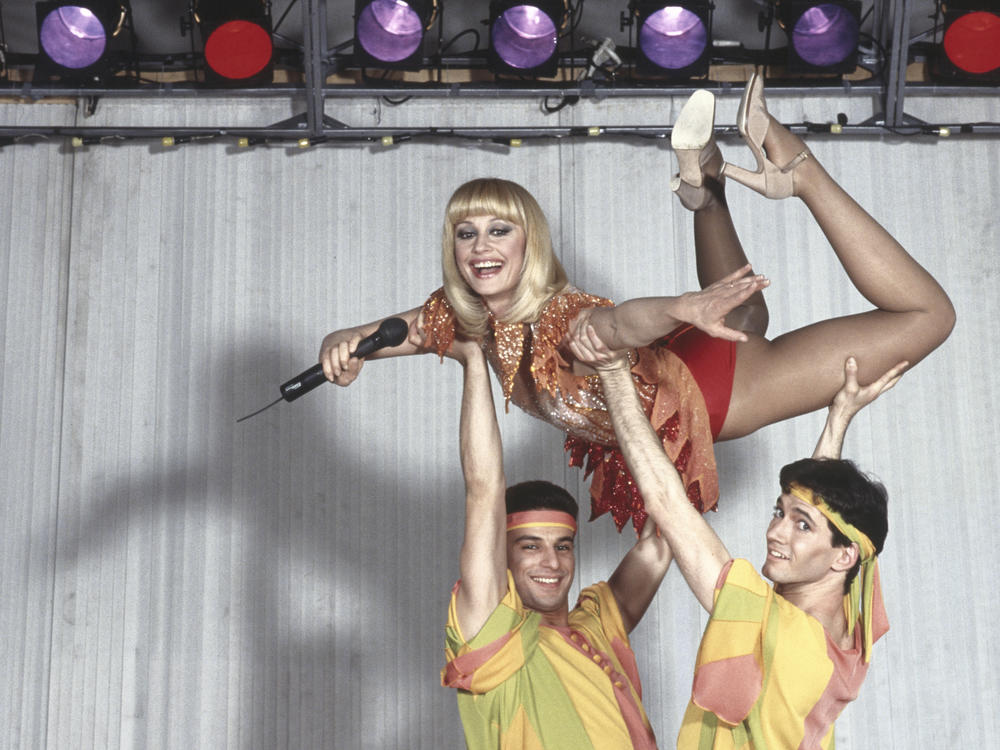 Italian singer and TV host Raffaella Carrà being lifted by dancers in a 1983 performance.