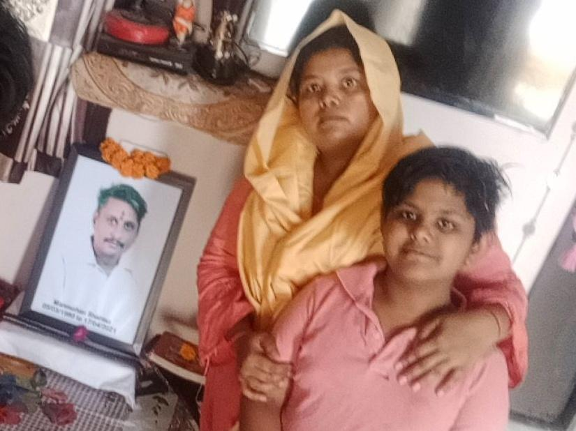 Pooja Sharma (center) and her two daughters, Lata, 14, and Yukti, 12, sit in front of a portrait of Sharma's late husband and the girls' father, Manmohan. He died from COVID-19 in April, leaving Sharma to fend for her family by herself.