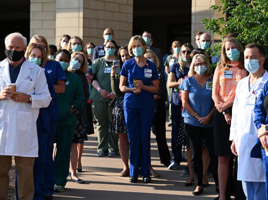 Front-line workers at a medical center in Aurora, Colo., gather for a COVID-19 memorial on July 15 to commemorate the lives lost in the coronavirus pandemic. New estimates say many thousands more will die in the U.S. this summer and fall.
