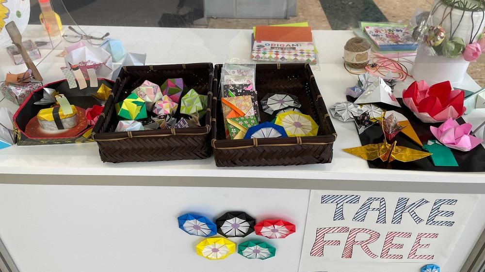 Volunteers make origami to give to visiting journalists at the Tokyo Olympics.