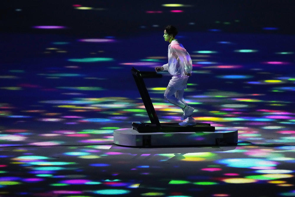 A lone athlete runs during the opening ceremony at the Olympic Stadium on Friday in Tokyo.
