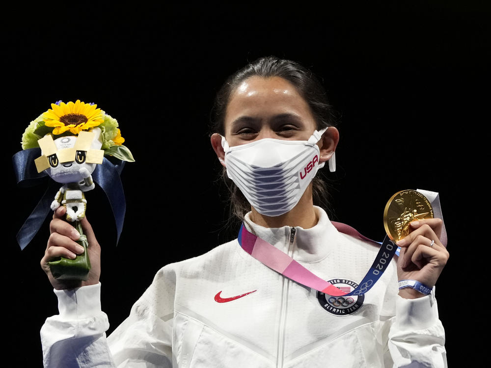 Gold medalist Lee Kiefer of the United States shows her medal and victory bouquet during the medal ceremony for the women's individual foil final competition on Sunday at the Summer Olympics.