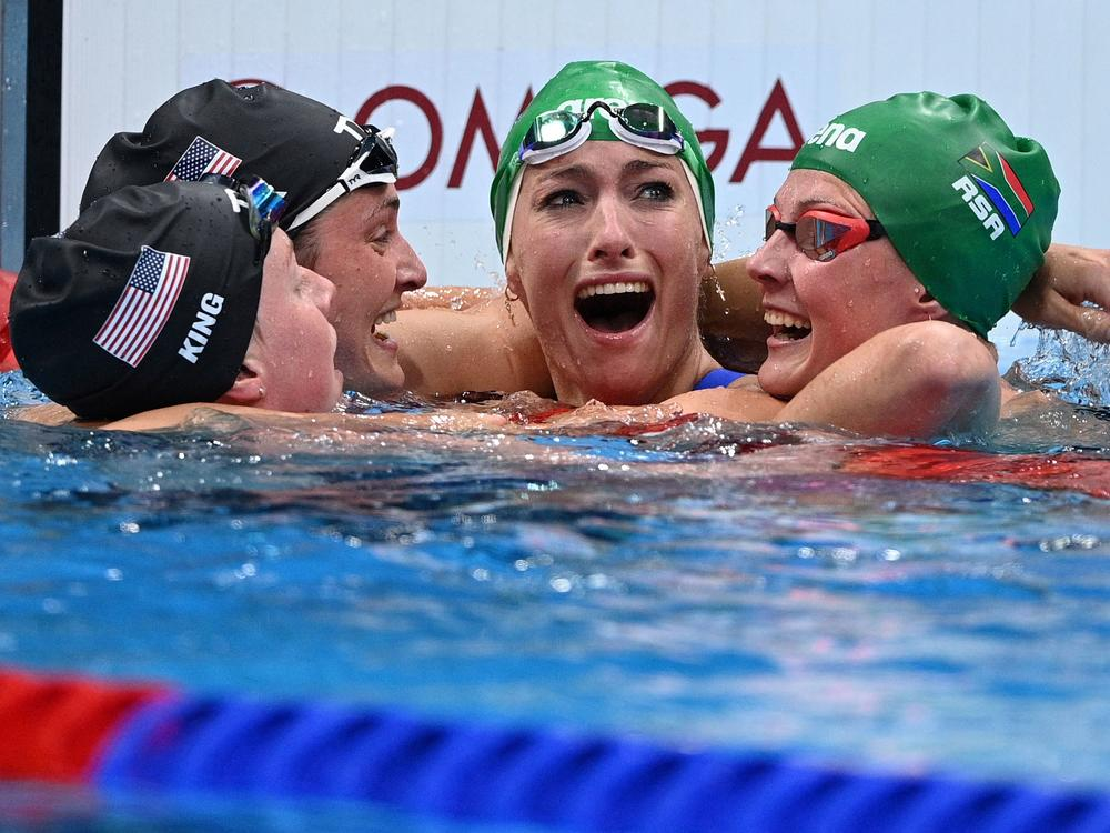 South Africa's Tatjana Schoenmaker, second from right, cheers with teammate Kaylene Corbett, right, and medalists Annie Lazor and Lilly King of Team USA after winning the final of the women's 200m breaststroke swimming event at the Tokyo Aquatics Centre on Friday.