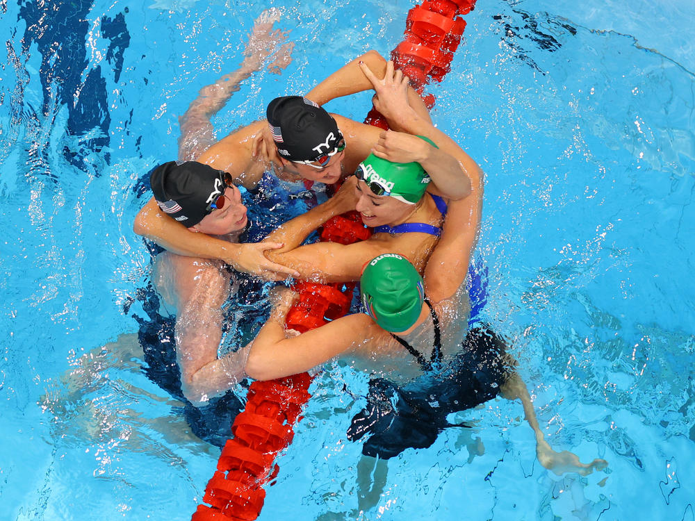 South Africa's Tatjana Schoenmaker is embraced by Lilly King and Annie Lazor of Team USA, and Kaylene Corbett of South Africa. Schoenmaker smashed a world record set in 2013.