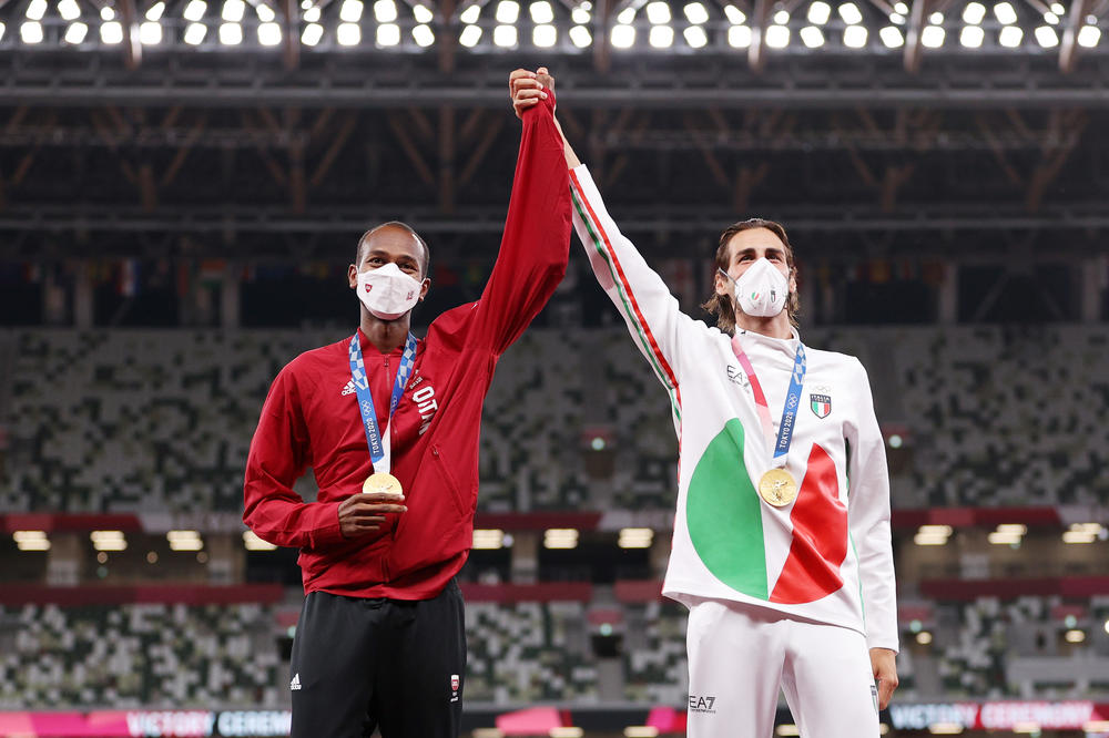 Joint gold medalists Mutaz Essa Barshim of Team Qatar and Gianmarco Tamberi of Team Italy celebrate on the podium during the medal ceremony for the men's high jump at the Tokyo Olympics.