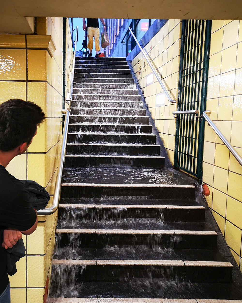 Water runs down the steps of a subway station in Berlin in 2019. Cities in the U.S. and Europe are racing to waterproof older subway systems as climate change drives more rain.
