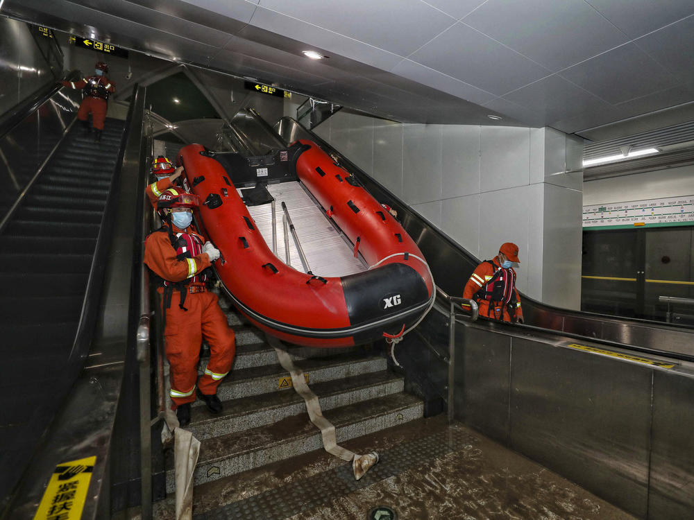 Rescuers carry a boat into the subway in Zhengzhou, China, in July after flash floods trapped passengers underground.