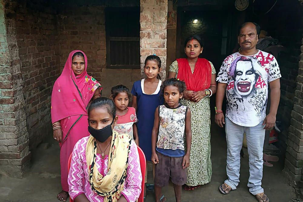 Jyoti Kumari (center, foreground, in mask) and family members stand in front of their house in Sirhulli, a village in eastern India.