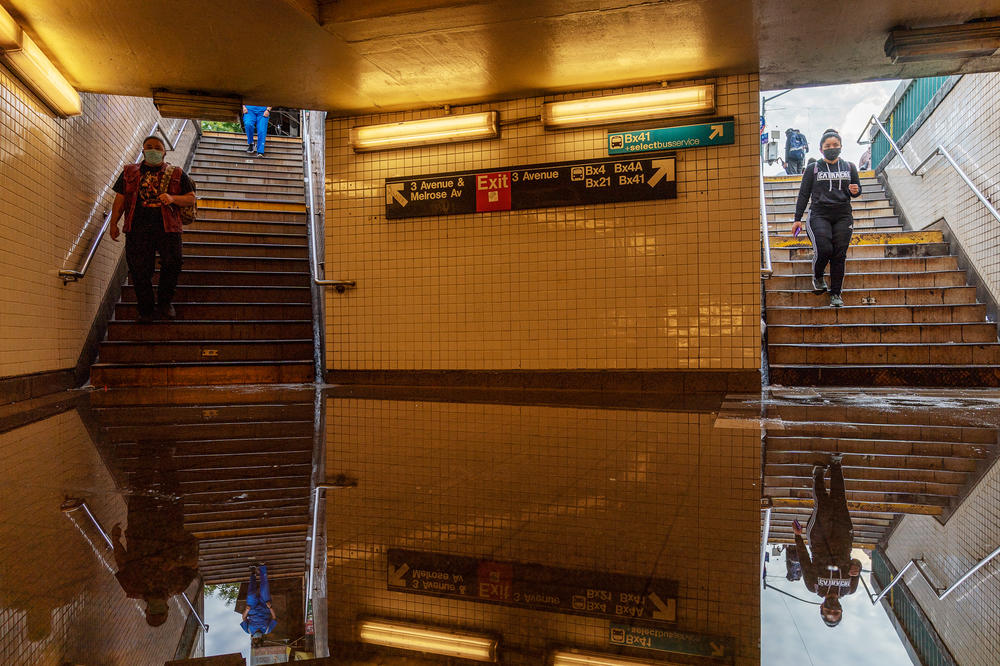 Commuters head into New York's Third Avenue-149th Street subway station on Thursday. Heavy rain from remnants of Hurricane Ida flooded much of the city's subway system. Authorities issued a travel ban and warned residents to avoid stations.