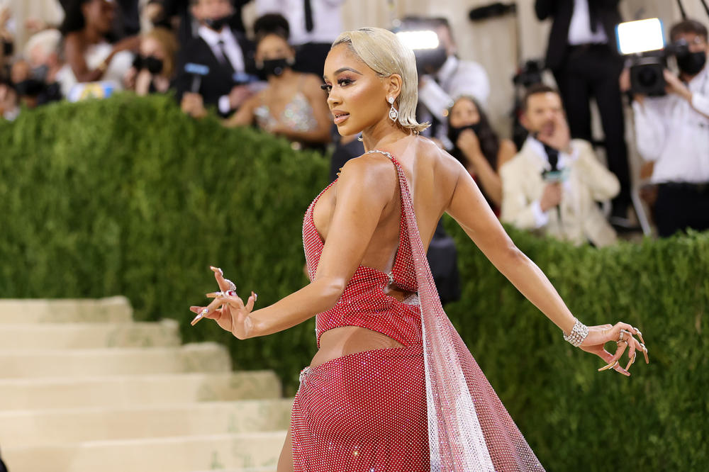 Saweetie told red carpet host Keke Palmer that her Christian Cowan caped dress is inspired by the Black American heritage flag and the Filipino flag.