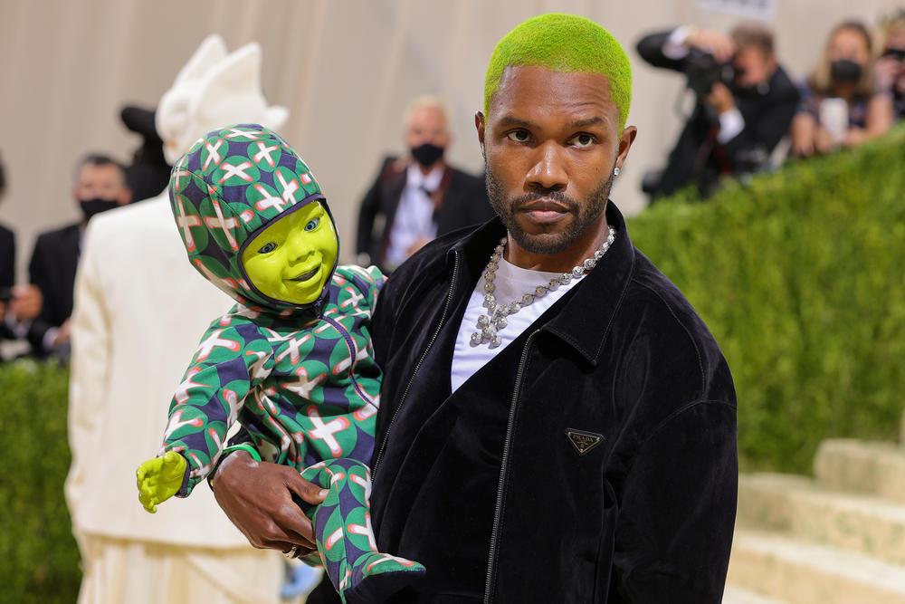 Frank Ocean, wearing a Prada suit jacket, carries a ... green robot-puppet-doll? A <a href=