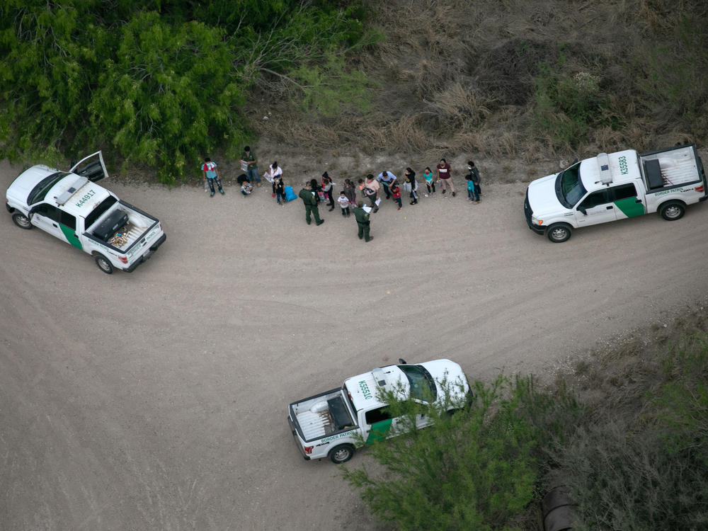 U.S. Border Patrol agents take asylum-seekers into custody as seen from a Texas Department of Public Safety helicopter near the U.S.-Mexico border on March 23 in McAllen, Texas.