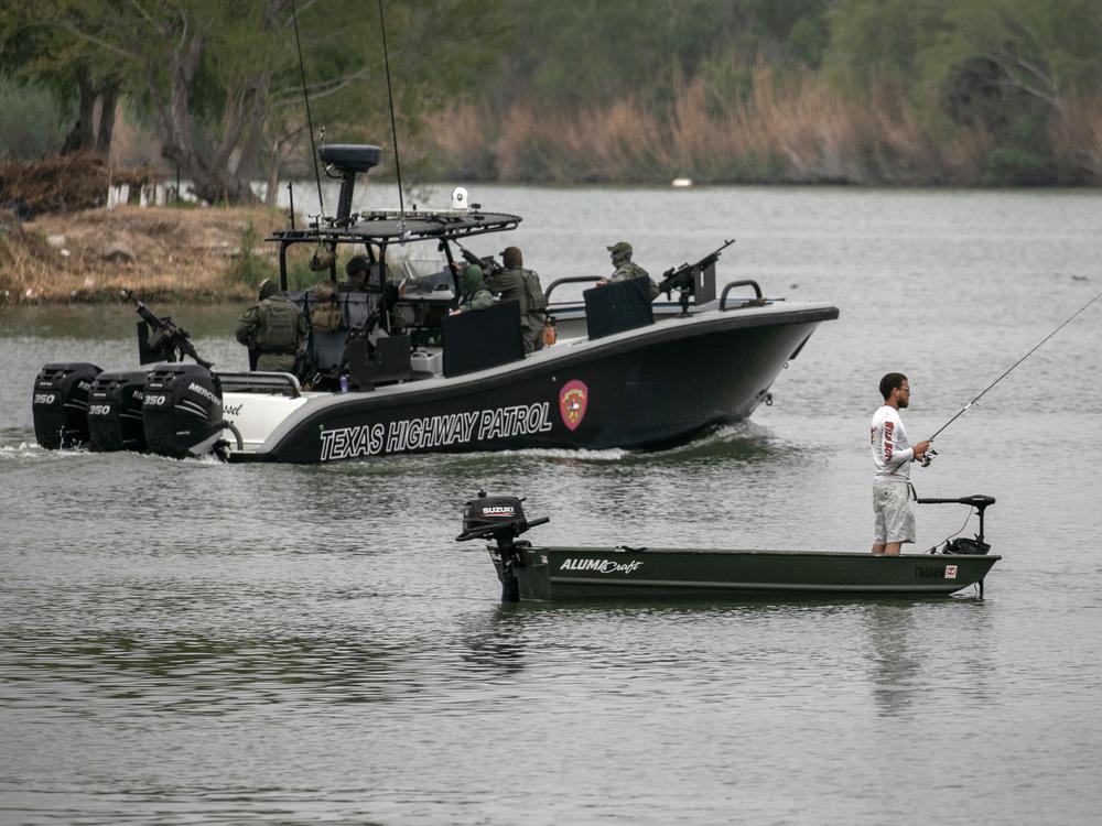 A Texas Department of Public Safety boat passes a Mexican fisherman on the Rio Grande on March 24 near Mission, Texas. Texas DPS troopers are taking part in Operation Lone Star.