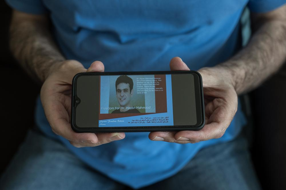 Hassan Mahmoud shows a cellphone image of a poster calling for freedom for his brother Hayan Mahmoud. Syrian officials told his family that Hayan had died in prison, but the family never found the body.