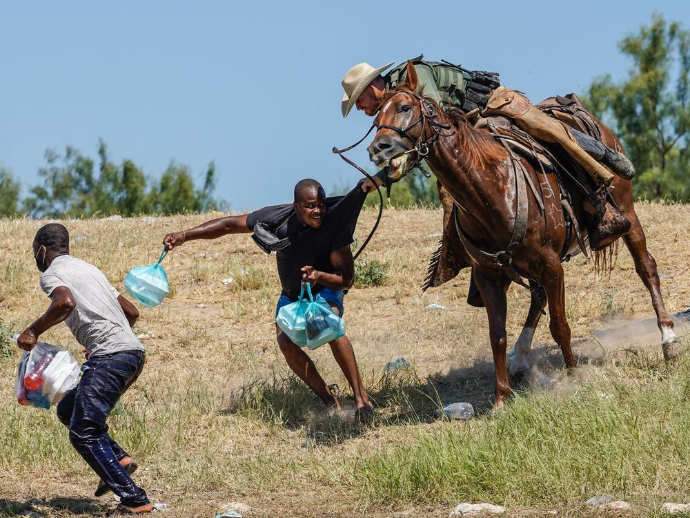 A U.S. Border Patrol agent on horseback tries to stop a Haitian migrant from entering an encampment on the banks of the Rio Grande on Sunday near the international bridge in Del Rio, Texas.