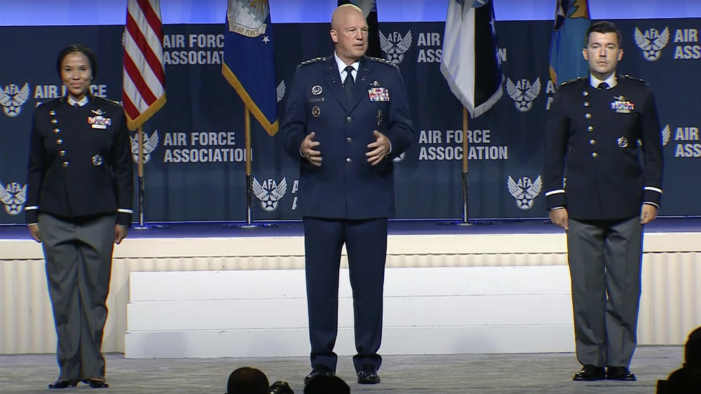 The chief of space operations, Gen. John Raymond, stands between two Space Force guardians as the branch unveils prototypes for its new service dress uniforms.