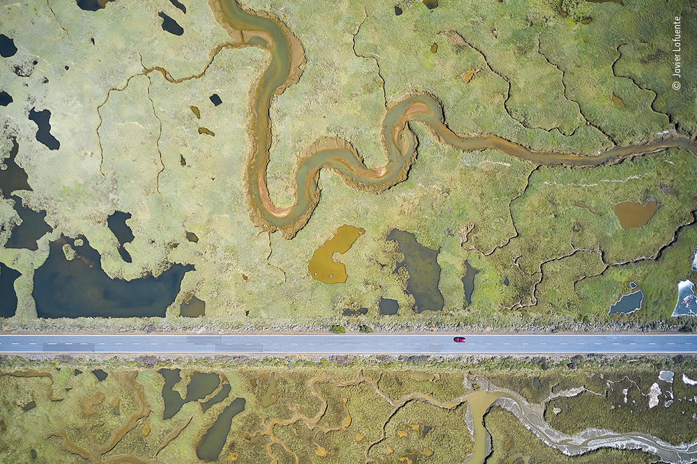 <em>Road to ruin</em>, by Javier Lafuente, Spain, winner, category: Wetlands - The Bigger Picture. Lafuente shows the stark, straight line of a road slicing through the curves of a wetland landscape. By maneuvering his drone and inclining the camera, Lafuente dealt with the challenges of sunlight reflected by the water and ever-changing light conditions.