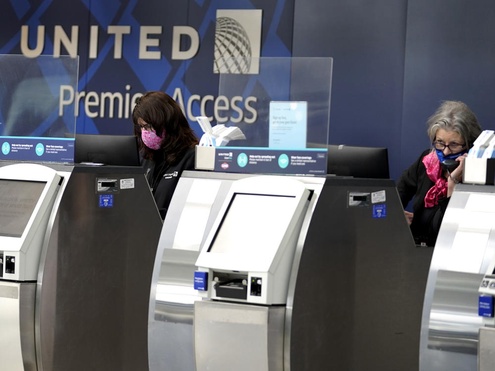 In this Oct. 14, 2020 file photo, United Airlines employees work at ticket counters in Terminal 1 at O'Hare International Airport in Chicago.