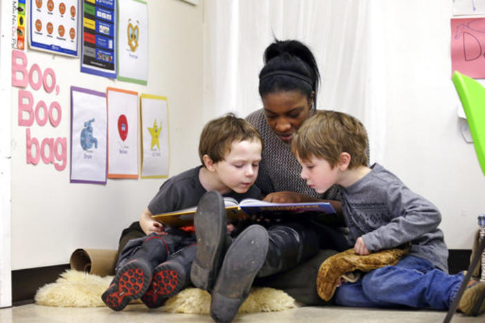 A woman reads to two children