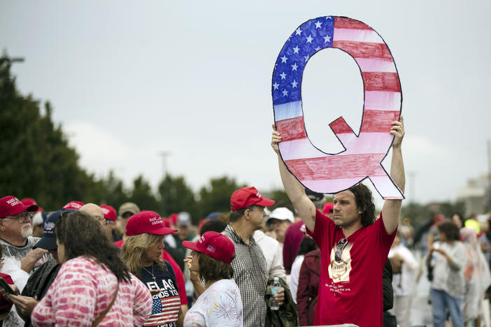 "A man in a red shirt holding up a large ""Q"" shaped sign in a protest. The ""Q"" is colored in with the shapes and colors of the American flag. Other protesters around him wear red MAGA hats."