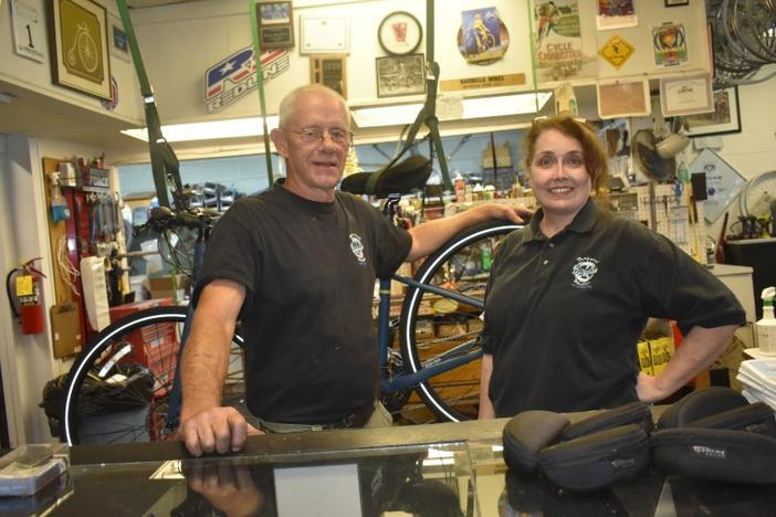 Mikki and Allen Griffin stand behind the counter of Perpetual Motion Bicycles in Carrollton. A pandemic rush on bikes has left them with few new bikes to sell, but plenty of demand for repairs.
