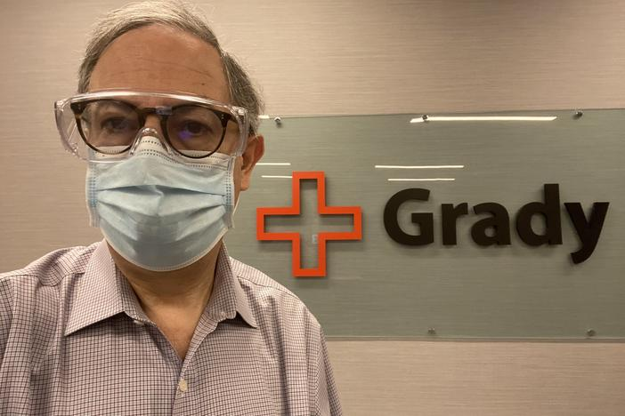 Dr. Carlos del Rio wears a mask in front of a Grady hospital sign.