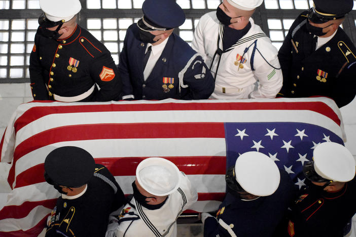 A military honor guard carries the casket of Rep. John Lewis into the Georgia State Capitol.