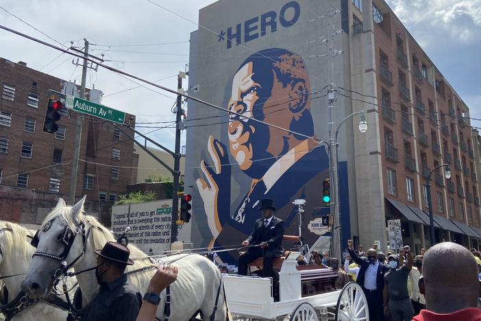 John Lewis' casket passes by his mural in Atlanta.