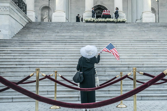 Woman waves flag outside US Capitol where Casket of John Lewis is on display