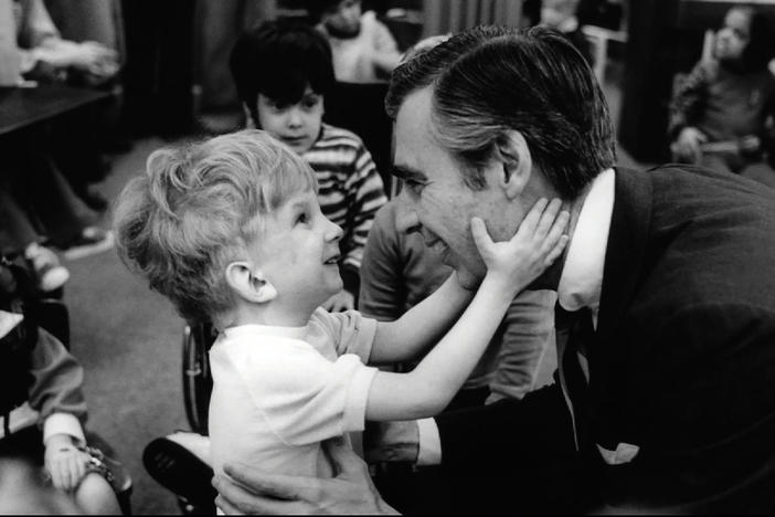 Fred Rogers and a young child.