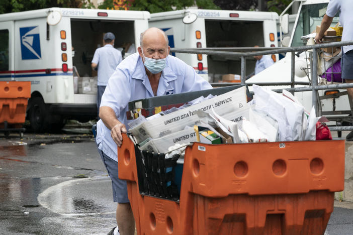 A male U.S. postal worker pushes an orange cart of letter mail towards the camera on a wet day. In the background, two other postal workers unload U.S. Postal Service trucks of mail.