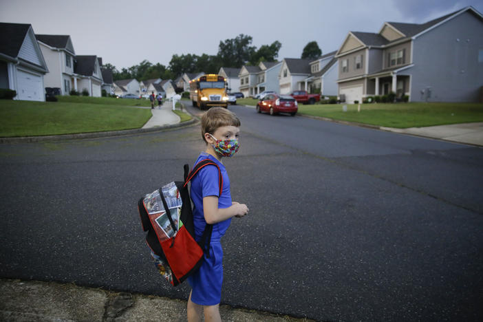 A child stands near a school bus.