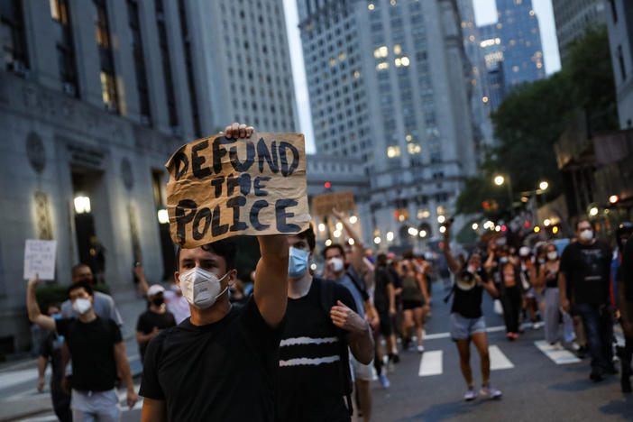 "A man at a protest holds a sign that reads ""Defund the Police."""