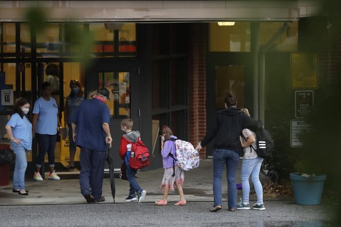 Students arrive to Dallas Elementary School for the first day of school amid the coronavirus outbreak on Monday, Aug. 3, 2020, in Dallas, Ga.