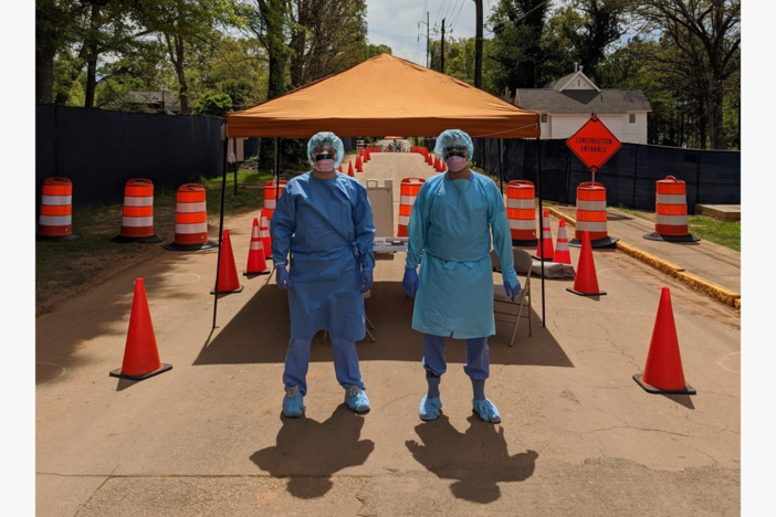 Two doctors with blue hairnets, blue medical scrubs, and masks stand in front of an orange medical tent surrounded by orange traffic cones.