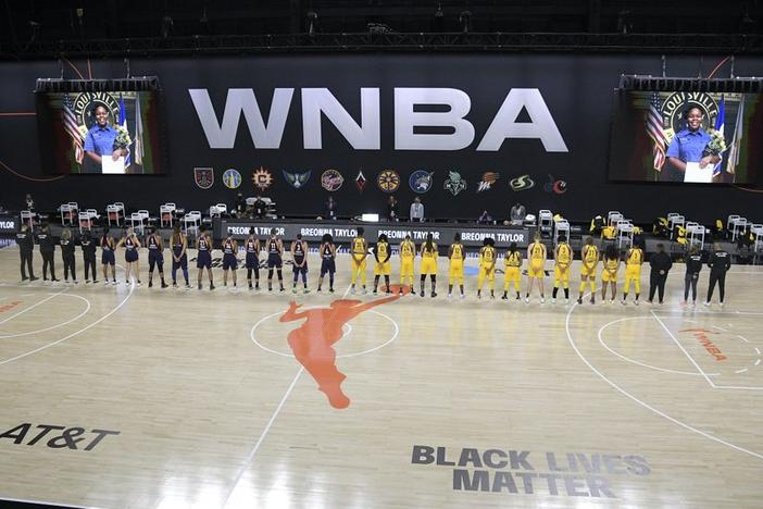 Members of the Phoenix Mercury, left, and Los Angeles Sparks stand for a moment of silence in honor of Breonna Taylor before a WNBA basketball game, Saturday, July 25, 2020.