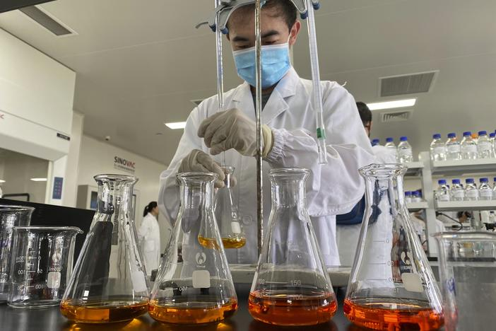 A worker works inside a lab at the SinoVac vaccine factory in Beijing on Thursday, Sept. 24, 2020. SinoVac, one of China's pharmaceutical companies behind a leading COVID-19 vaccine candidate, says its vaccine will be ready by early 2021 for distribution worldwide, including the U.S.