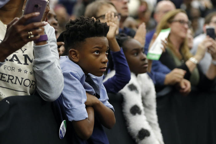 A young child watches as former President Barack Obama steps on stage to speak during a campaign rally for Georgia gubernatorial candidate Stacey Abrams at Morehouse College Friday, Nov. 2, 2018, in Atlanta. (AP Photo/John Bazemore)