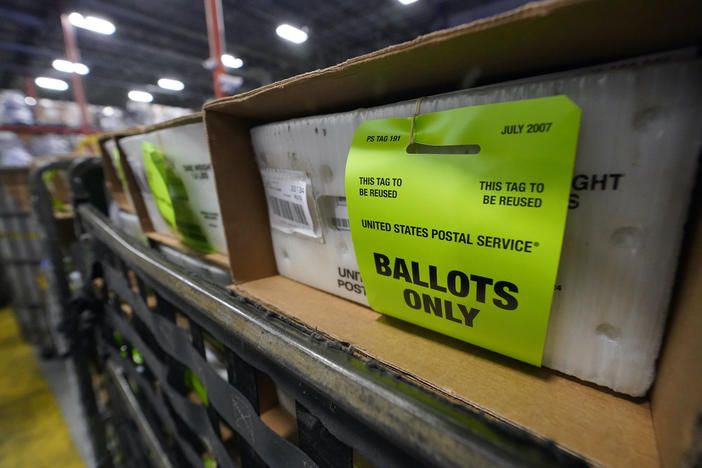 A cart holding vote-by-mail ballots is seen before being loaded into a truck for transport to a local U.S. Postal Service office, Thursday, Oct. 1, 2020, at the Miami-Dade County Elections Department in Doral, Fla.