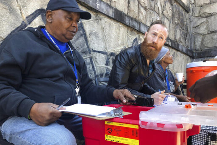 In this photo from March 20, 2019, Harry Ethridge, client services manager at the Atlanta Harm Reduction Coalition, and Jonathan Spuhler, an outreach coordinator for Absolute Care and volunteer at AHRC, set up a needle exchange station for drug users to swap out used syringes for clean syringes on English Avenue in Atlanta.