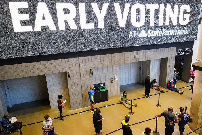 People wait in line to vote early at the State Farm Arena on Monday, Oct. 12, 2020, in Atlanta.