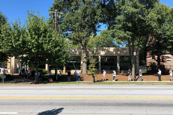 Voters stand outside Fulton County Library System's Ponce De Leon Branch to vote during the first week of in-person early voting.