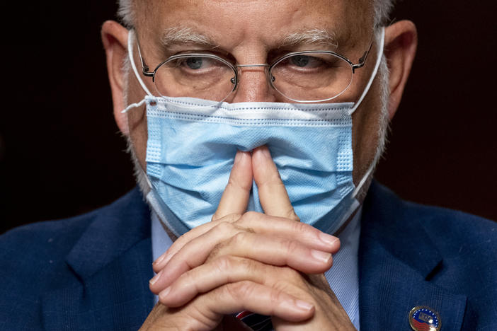 Dr. Robert Redfield wears a mask with his hands in front of his mouth.